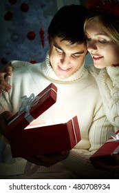 Young couple sitting in the dark and opening a gift box lit inside