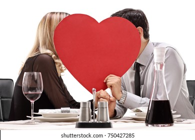 Young couple sitting at a dinner table and kissing behind a red heart isolated on white background