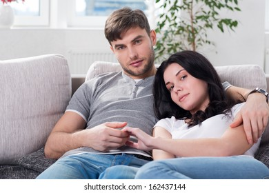 young couple are sitting down on a couch embracing each other