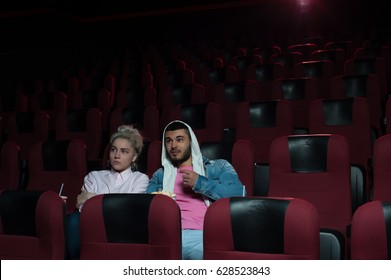 Young couple sitting in empty cinema theater