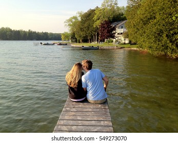 Young couple sitting at end of dock lakeside
