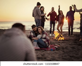 Young Couple Sitting with friends Around Campfire on The Beach At sunset drinking beer colored filter