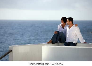 Young couple sitting in front of the sea