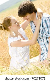 young couple sitting in grain field