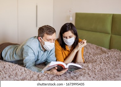 A young couple is sitting at home on self-quarantine. Husband and wife quarantined  coronavirus in protective masks. New reality. Normal life in isolation. Read a book together. Italy europe covid-19