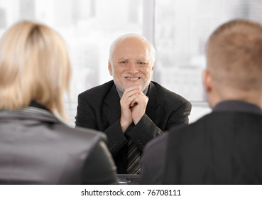 Young couple sitting at lawyer's office, senior lawyer looking at camera, smiling.?