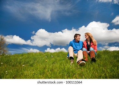 Young couple sitting in nature grass landscape