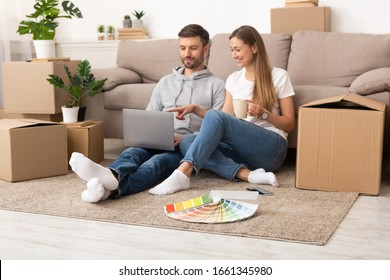 Young couple sitting in new apartment with unpacked boxes and looking at laptop choosing color for living room