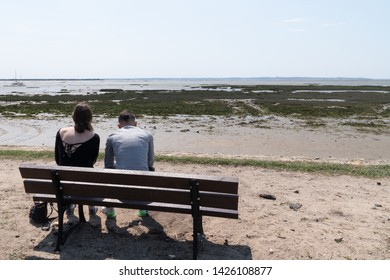 young couple sitting on beach bench in summer sea background low tide