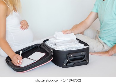 Young couple sitting on bed and packing baby clothes. Pregnant woman hand holding notebook with list and man checking things. Preparing for hospital childbirth or traveling.