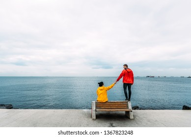 Young couple sitting on a bench by the sea. Man and woman traveling. People sit on a bench and look at the sea. Tourists by the sea. Friends on the bench. A lonely pair. Walking along the promenade