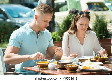 Young Couple Sitting On Bench Having Lunch Together