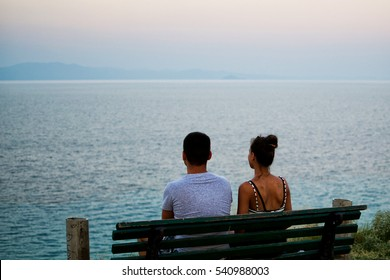 Young couple sitting on a bench and enjoy the beautiful view of the sea