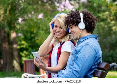 Young couple sitting on the bench and listening music over headphones and smile