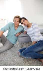 Young couple sitting on carpet at home