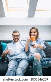 Young couple sitting on the couch, drinking coffee and watching tv