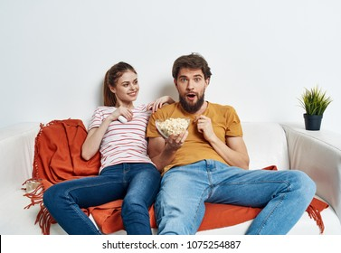 young couple sitting on the couch, emotional man eating popcorn