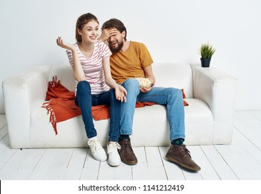young couple sitting on couch emotions
