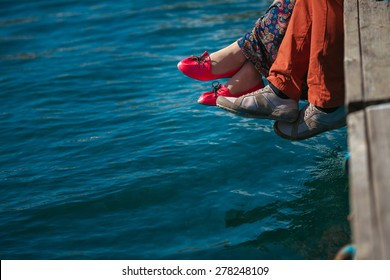 Young couple sitting on the dock by the sea background, feet closeup