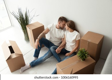 Young couple sitting on the floor with cardboard boxes bonding holding hands, happy man and woman enjoy moving day in new unfurnished rental bought apartment, homeowners relocation into own house