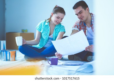 Young couple sitting on floor and calculating about they savings. Young couple