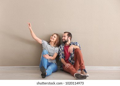 Young couple sitting on floor in empty room. Ready for moving to new house