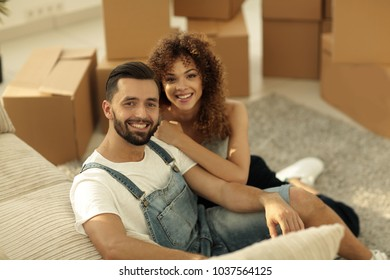 Young couple sitting on the floor in a new apartment