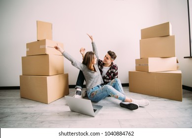 Young couple sitting on the floor happy with raised hands looking on laptop after moving in new apparment.