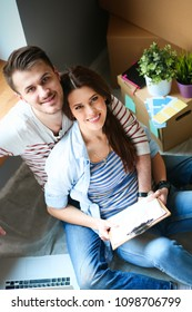 Young couple sitting on the floor of their new apartment. Young couple