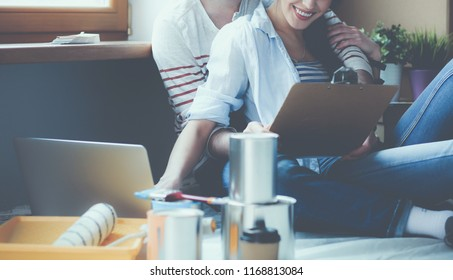 Young couple sitting on the floor of their new apartment