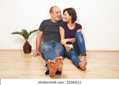 A young couple sitting on the floor in their living room. The young woman is laughing.