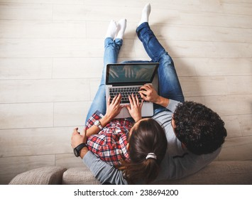 Young couple sitting on floor and using notebook.Online shopping.