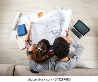 Young couple sitting on floor and  calculating about they savings.They plan to invest in new house.View from above.