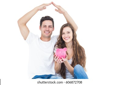 Young couple sitting on floor with piggy bank on white background