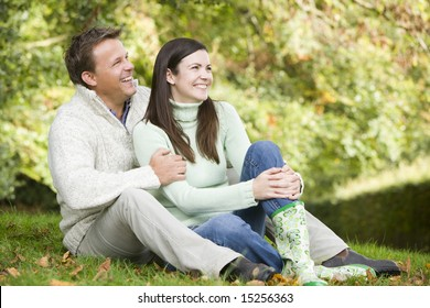Young couple sitting on grass in autumn woods