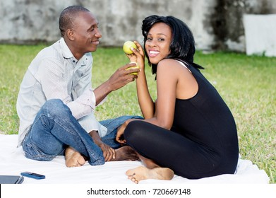 young couple sitting on the grass sharing a green apple together lovingly