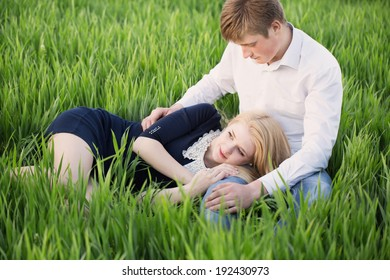 young couple sitting on green grass