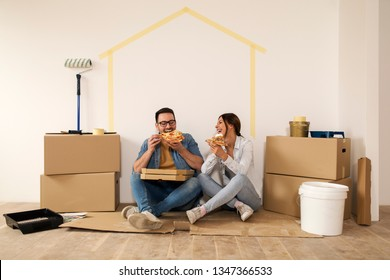 Young couple sitting on ground eating pizza and making a break from moving-in new apartment.