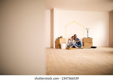 Young couple sitting on the ground making a break from moving-in in their new apartment.