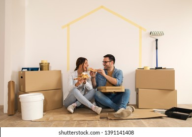 Young couple sitting on the ground making a break from moving-in while man giving a bite of pizza to his girlfriend.