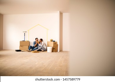 Young couple sitting on a ground in their new apartment and sharing a slice of pizza.