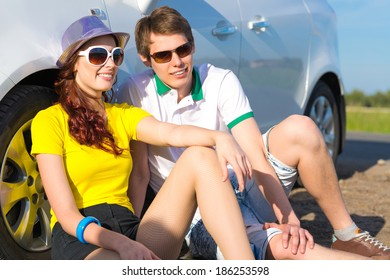 young couple sitting on the ground next to the wheel of a car, a summer road trip