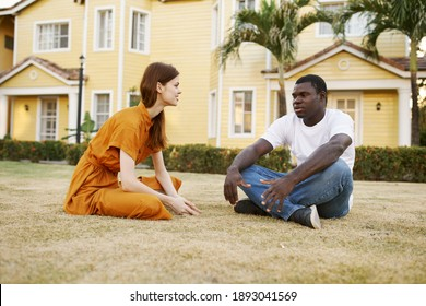 young couple sitting on the ground chatting outdoors