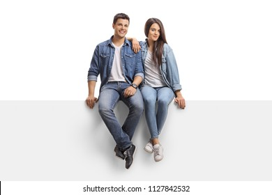 Young couple sitting on a panel and looking at the camera isolated on white background