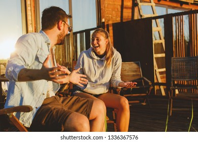 Young couple sitting on the porch and laughing during the sunset