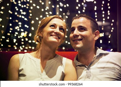 young couple sitting on a red couch