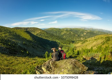 young couple sitting on the rock in the mountains view