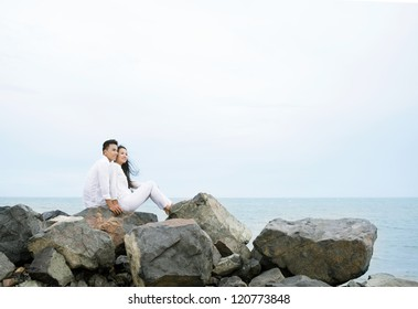 Young couple sitting on rocks and looking at the sea