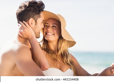 Young couple sitting on sand on the beach