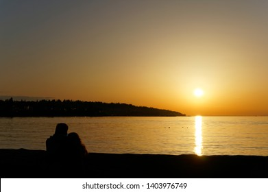 Young couple sitting on the seashore silhouetted by the sun setting over the ocean